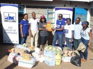 Joseph Waithaka, Head of Diaspora Banking (center) presents food stuffs to Eunice Menja (3rd left), the founder of the Upendo Children's home as ABC Bank staff look on.