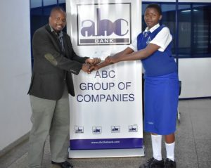 Head of Risk & Compliance John Rioba (left) present a school fees cheque to Eliza Rhobi Mwita (right).