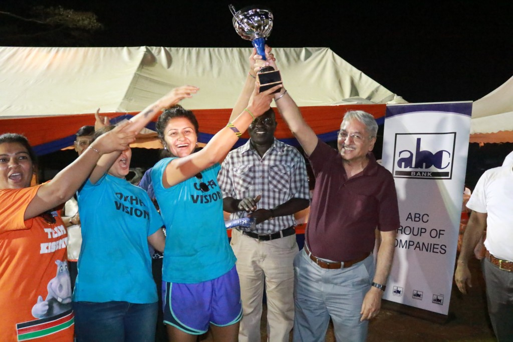 Mr. Raj Arora, ABC Bank's chief credit officer, presents an award during the event as Mr. Douglas Okiring' ABC Bank Kisumu Branch manager looks on.