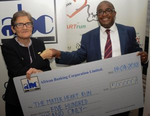 ABC Bank General Manager - Treasury and Financial Institutions Philip Wambua (right) presents a dummy cheque to Sister Brigid Marnane (left) of Mater Hospital in support of The Mater Heart Run 2018